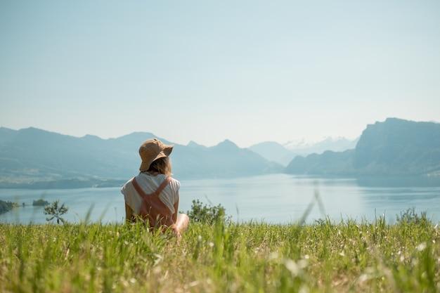 Menina sentada no gramado verde perto do lago