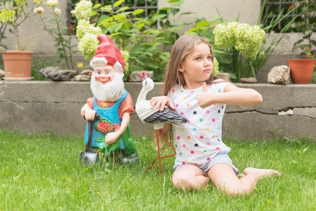 Menina sentada no jardim mostrando o polegar para cima o sinal