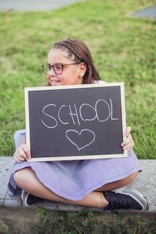 Menina sentada no parque com sinal de amor da escola
