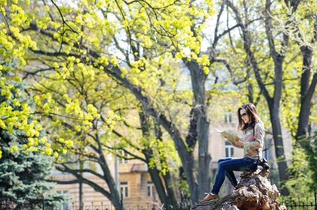 Menina sentada no parque e lendo um mapa