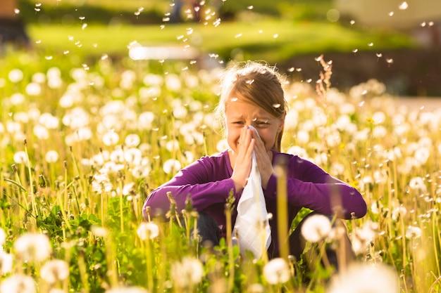 Menina sentada no prado com dentes de leão e tem febre do feno ou alergia
