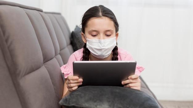 Menina sentada no sofá com tablet