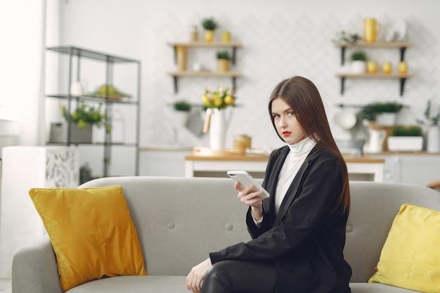 Menina sentada no sofá e use o telefone