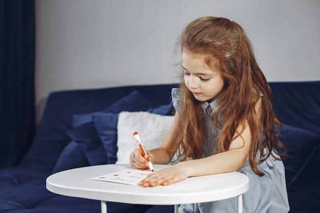 Menina sentada no sofá. sofá azul. criança desenha.