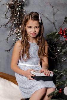 Menina sentada perto da árvore de natal na véspera de natal, segurando uma caixa de presente
