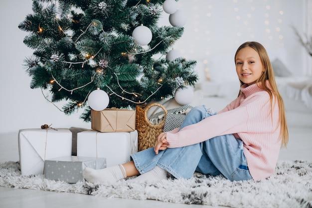 Menina sentada perto da árvore de natal