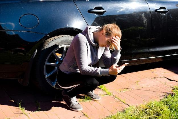 Menina sentada perto de um carro quebrado, esperando por assistência na estrada