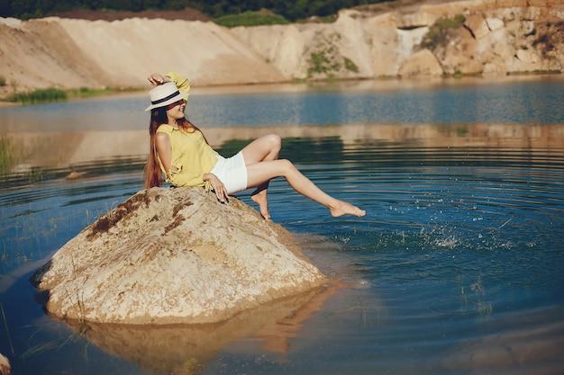 Menina sentada perto do rio