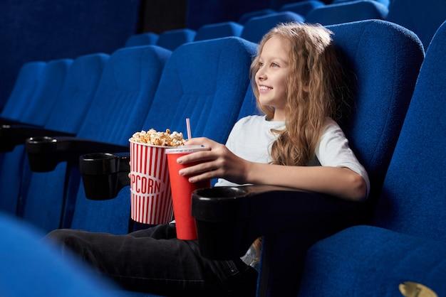 Menina sentada sozinha no cinema e assistindo filme cômico