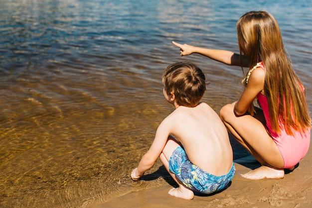 Menina, sentando, com, menino, e, apontar, afastado, em, litoral