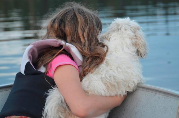 Menina, sentando, com, um, cão, ligado, a, bote, lago, de, a, madeiras, ontário, canadá
