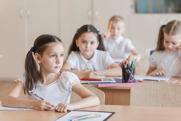 Menina, sentando, em, lição, e, olhando