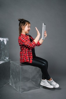 Menina, sentando, ligado, bloco, tendo, chamada vídeo, através, pc, tabuleta, waving, mão