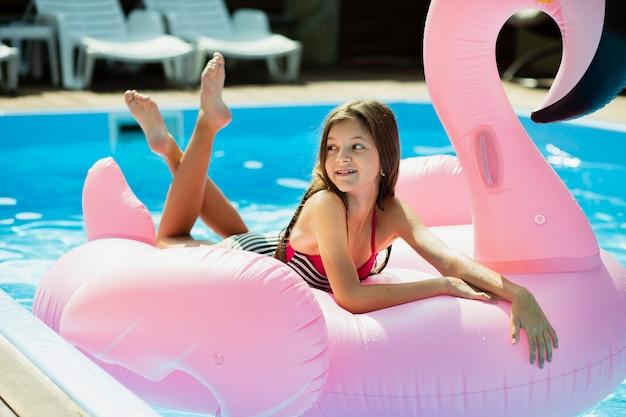Menina, sentando, ligado, um, flamingo, floatie, e, olhando