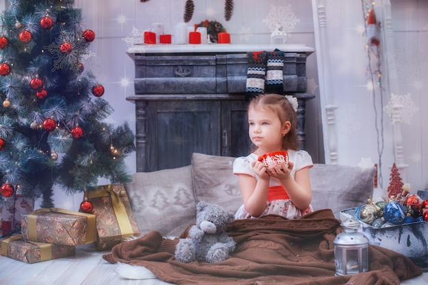 Menina, sentando, perto, árvore natal, embrulhado, pernas, em, um, cobertor
