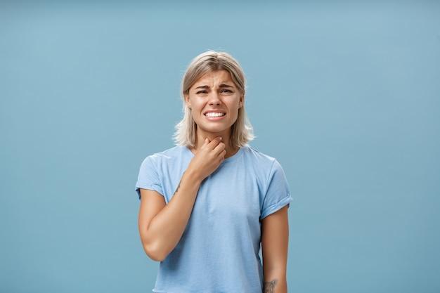 Menina sentindo desconforto na garganta, pegando um resfriado ou tendo alergia sazonal tocando o pescoço