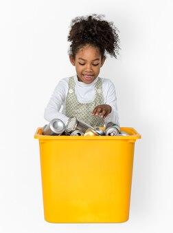 Menina, separando o metal reciclável pode retrato de estúdio