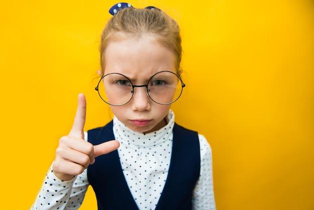 Menina séria e engraçada com o dedo indicador amarelo