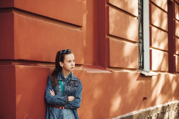 Menina séria em roupas jeans fica perto de um antigo prédio bonito restaurado