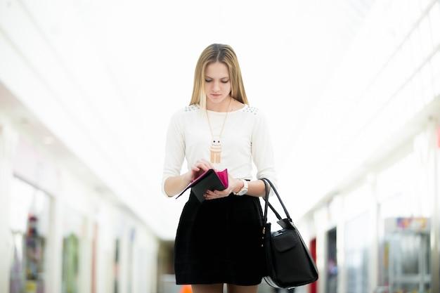 Menina séria que olha dentro de sua bolsa