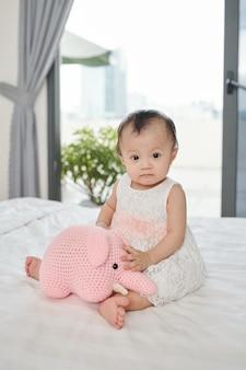 Menina séria sentada na cama brincando com seu brinquedo favorito