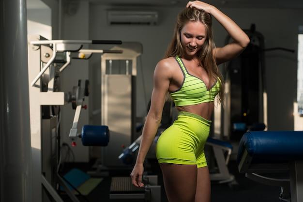 Menina sexy muscular atlética bonita a menina está levantando após um exercício