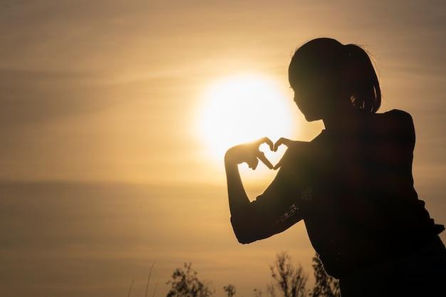 Menina silhueta usando dedo para fazer coração com lindo pôr do sol
