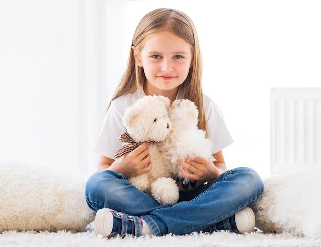 Menina simpática brincando de brinquedos na sala de luz