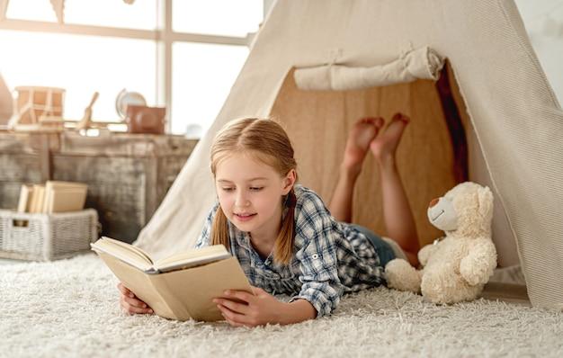 Menina simpática com urso e livro de papel sentada no chão da sala decorada com cabana, baú e lanterna retrô