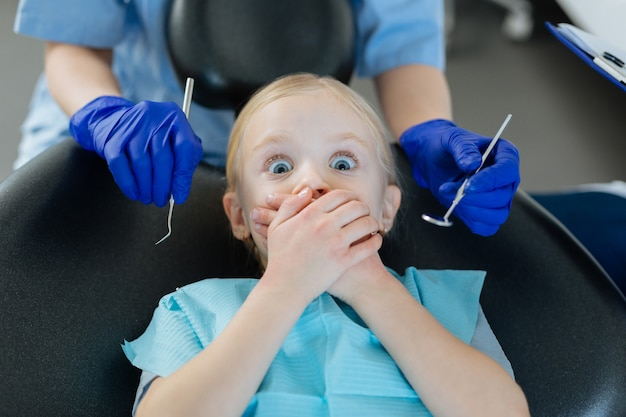 Menina simpática deitada em uma cadeira de dentista e cobrindo a boca, com medo do check-up no dentista