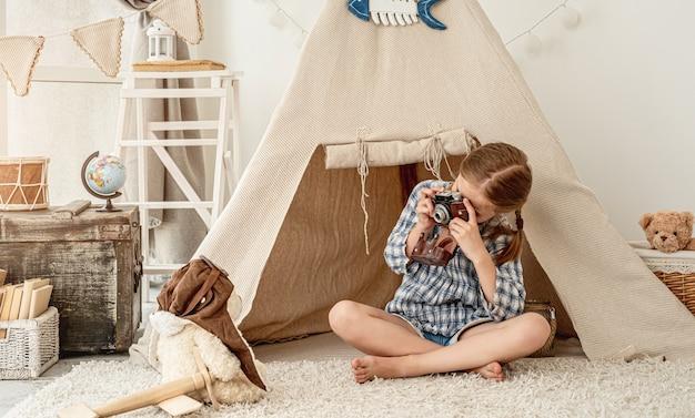 Menina simpática fotografando ursinho de pelúcia em cabana instalada na sala de jogos
