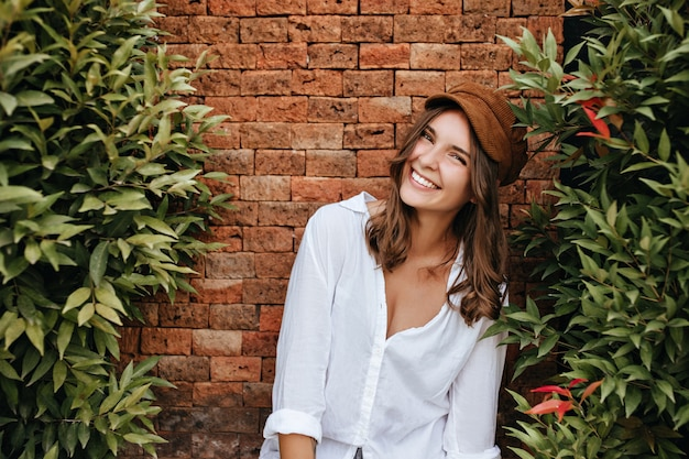 Menina sincera de boné marrom e blusa branca ri, apoiada na cerca de tijolos. foto de uma mulher bronzeada com um sorriso branco como a neve entre arbustos verdes.