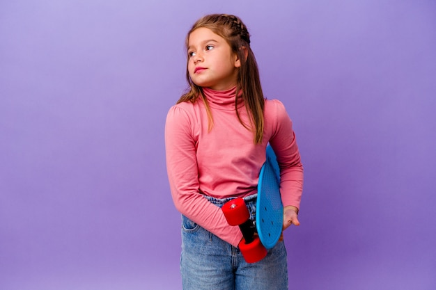 Menina skatista caucasiana isolada na parede azul sonhando em alcançar objetivos e propósitos