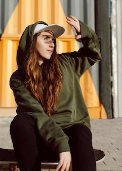Menina skatista escondendo o rosto do sol com a cabeça