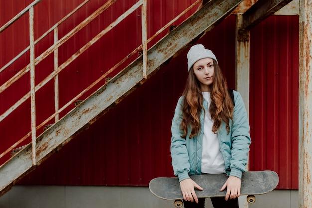 Menina skatista segurando o skate na frente dela