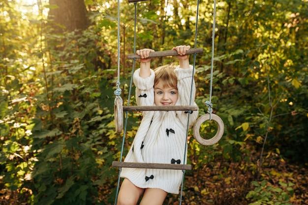 Menina sobe por escada de corda no jardim. criança do sexo feminino posa no quintal. criança se divertindo no parquinho ao ar livre, infância feliz