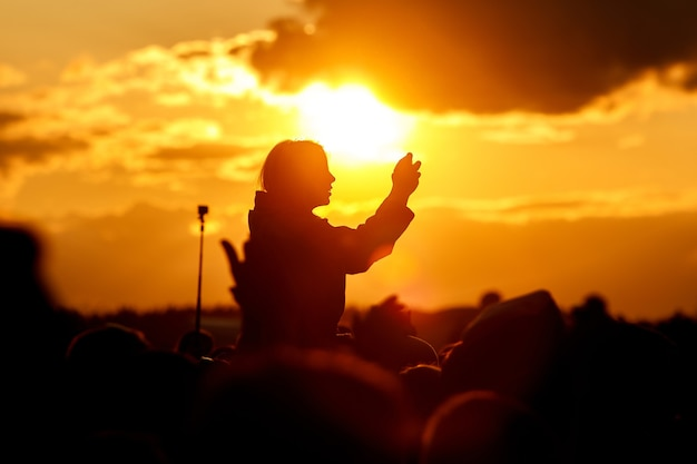 Menina sobre a multidão contra o céu do sol. se divertindo e usando seu smartphone no festival de verão.