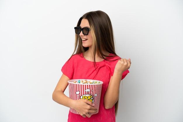 Menina sobre fundo branco isolado com óculos 3d e segurando um grande balde de pipocas enquanto olha para o lado