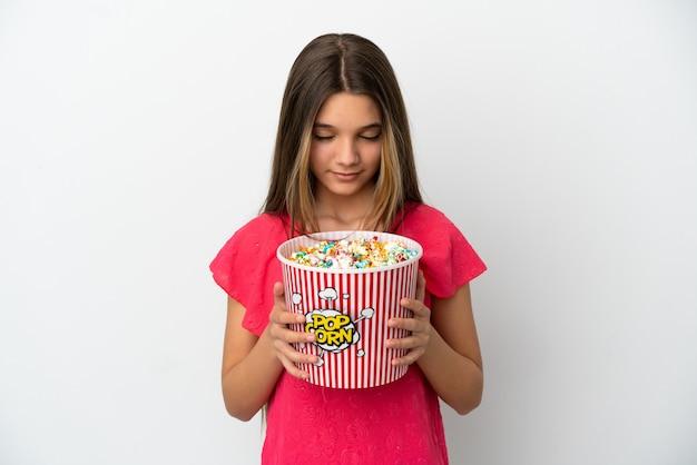 Menina sobre fundo branco isolado segurando um grande balde de pipocas