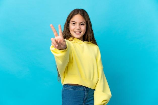 Menina sobre o azul isolado sorrindo e mostrando o sinal da vitória