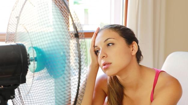 Menina sofrendo de uma onda de calor, usando um ventilador, sentada no sofá da sala de estar em casa.