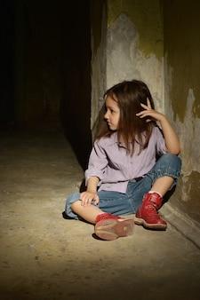 Menina solitária em um porão escuro