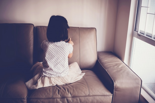 Menina solitária jogando sozinha no sofá em casa, austism e conceito de saúde mental infantil