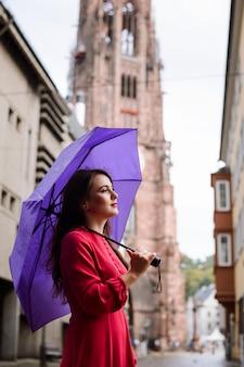 Menina sonhadora calma tendo um passeio na cidade enquanto chove