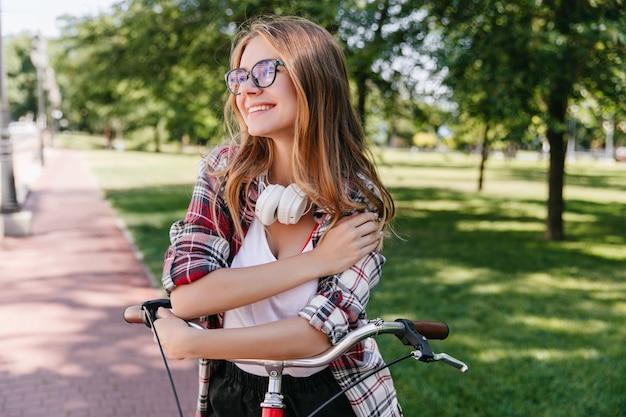 Menina sonhadora caucasiana com bicicleta, olhando ao redor com um sorriso. muito jovem de óculos em pé no parque.