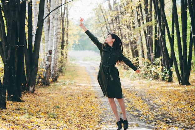 Menina sonhadora com cabelo preto longo natural voa no fundo do outono com árvores e folhas amarelas no bokeh.