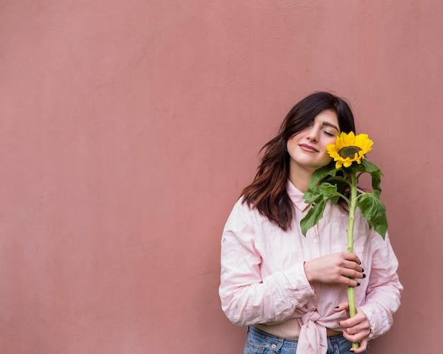 Menina sonhadora com girassol amarelo