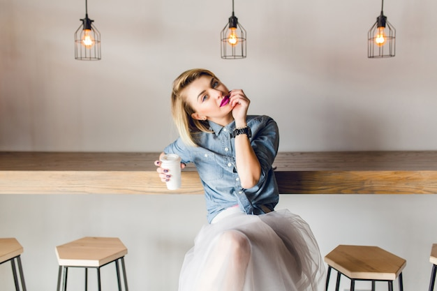 Menina sonhadora e elegante, com cabelo loiro e lábios cor de rosa, sentada em um café com cadeiras de madeira e mesa. ela segura uma xícara de café