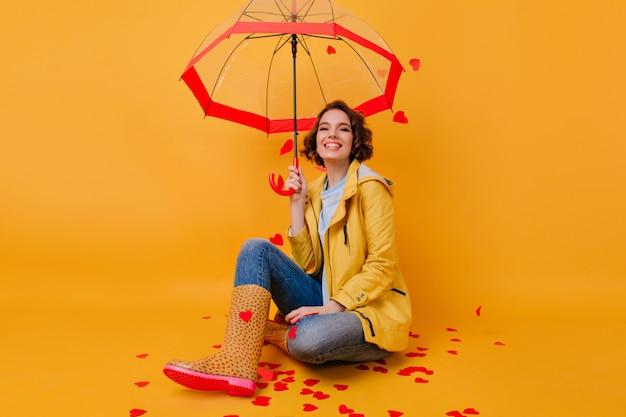 Menina sonhadora em sapatos de borracha engraçados, sentada com as pernas cruzadas na parede amarela. retrato interior de mulher romântica em jaqueta brilhante, posando com guarda-sol.