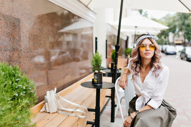 Menina sonhadora em uma camisa branca com uma pequena mochila esperando namorado em um café ao ar livre